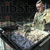 Mess: First Sgt. Mike Davis prepares sausage in the KP tent during Sunday morning's Victory Day event.