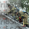 Vent: Two Terre Haute firefighters vent the roof of a house on fire in the 1400 block of Woodley Avenue Friday afternoon.