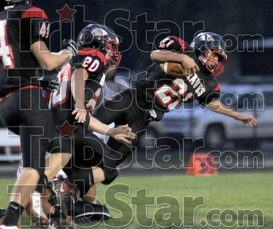 Diving for yardage: South's #21, Dillon Carter dives for extra yards after being tacked around the ankles by a North Central defender Friday night.