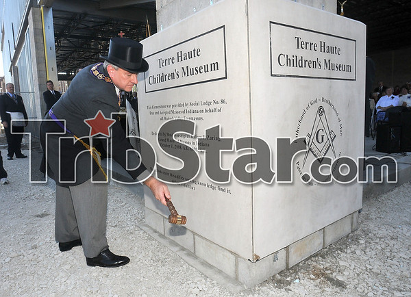 Dedicating it to the community: Jeffrey Zaring, grand master of the Grand Lodge of Free and Accepted Masons of Indiana, taps the cornerstone of the Terre Haute Children's Museum to symbolize the leveling of the stone Saturday.