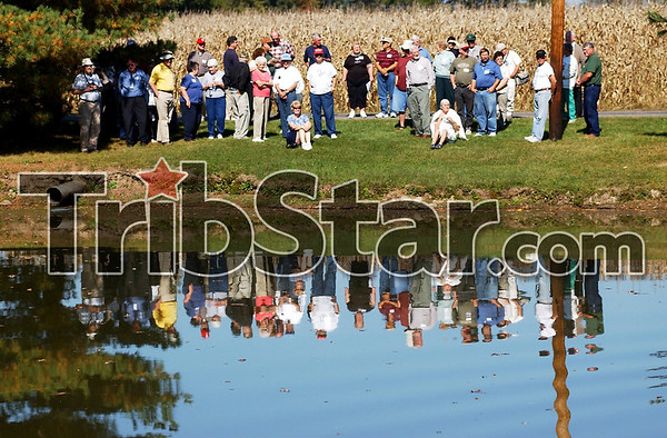 Refelcting on the past: members of the Indiana Canal Society tour look out over a section of the Wabash and Erie Canal off Woodsmall Raod east of SR159 Saturday afternoon.