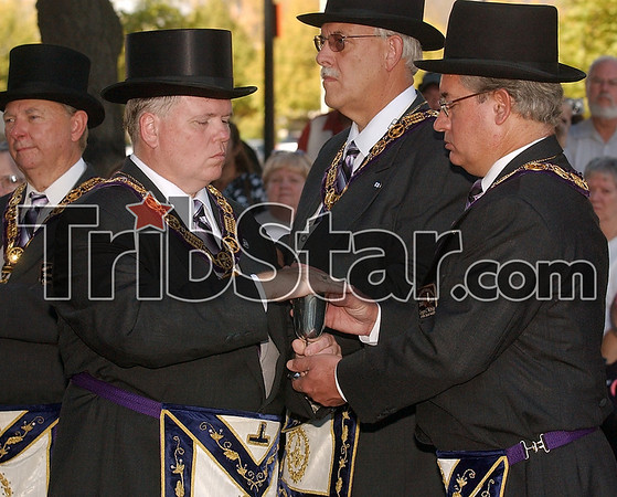 For the cornerstone: Grand Lodge Grand Marshal, Don Marcum, of Seymour, hands a cup of oil to Junior Grand Warden Gregg Walbridge of Fort Wayne during the Grand Lodge dedication of the cornerstone of the Terre Haute Children's Museum Saturday.