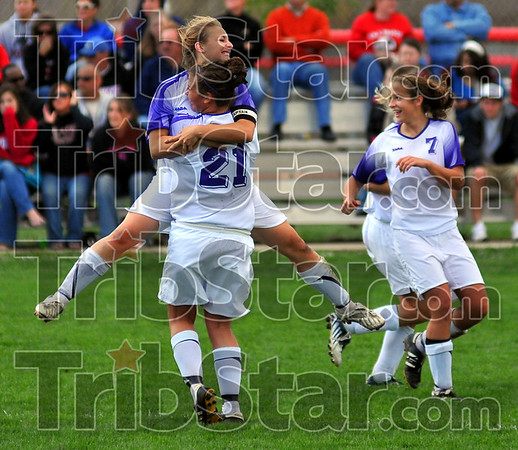 Winners: Greencastle's Rebecca Grivas jumps into the arms of teammate Hannah Deer (21) after scoring an insurance goal against Terre Haute South late in their sectional championship game Saturday afternoon. Also enjoying the moment is Melissa Ball (7).