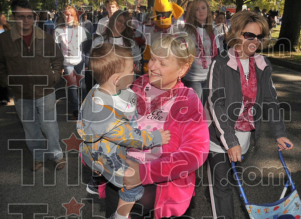 Walking with Jase: 18 year cancer survivor Sue Tyler carries her grandson, Jase Ruggles, 1, of Fishers during the Survivors Walk portion of the Race for the Cure Saturday at St. Mary-of-the-Woods College. At right, is Sue's daughter and Jase's mother, Stephanie Ruggles.