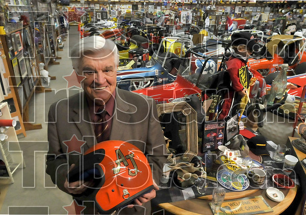 Quite the collection: First Financial Bank's Don Smith holds an A.J. Foyt helmet from his vast auto racing, sports and personal collection Wednesday in one of his garages near Riley.