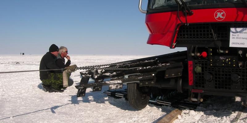 "Getting belts on the Pistenbully.<br /> <br /> Montering af bælter på Pistenbullyen<br /> <br /> Photo: Jim Hedfors (Swedish Geotechnical Institute), NEEM ice core drilling project,  <a href=""http://www.neem.ku.dk"">http://www.neem.ku.dk</a>"