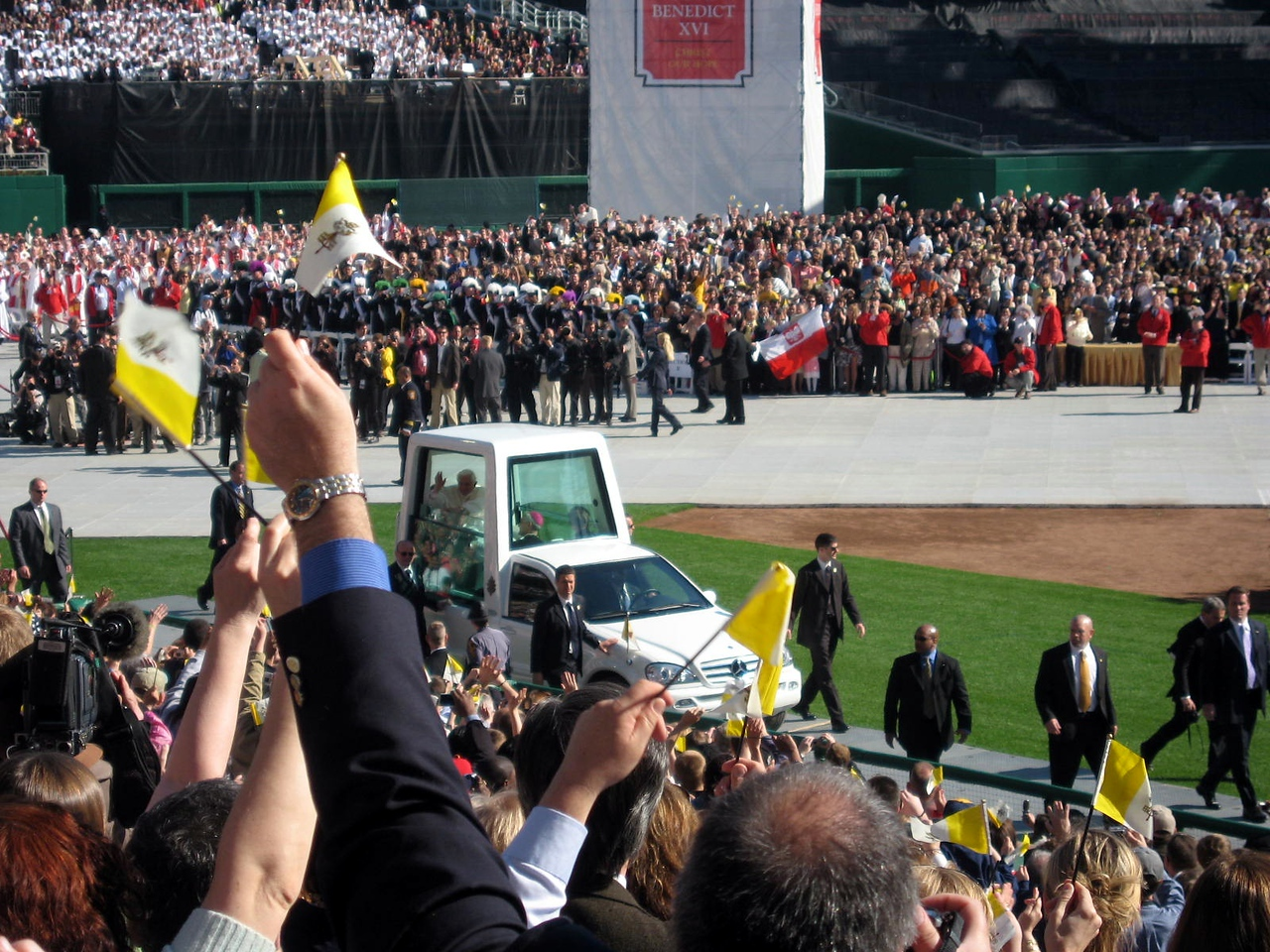 The crowd cheers as Pope Benedict XVI enters the stadium in the popemobile