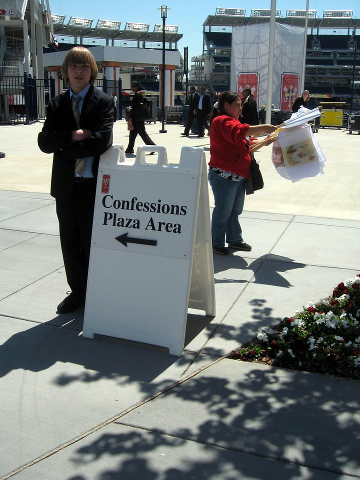 Sign directing attendees to the approximately 100 priests hearing confessions before the Mass.