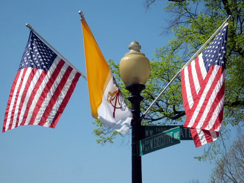 The flag of the United States and the flag of the Vatican City, on a street light at the White House