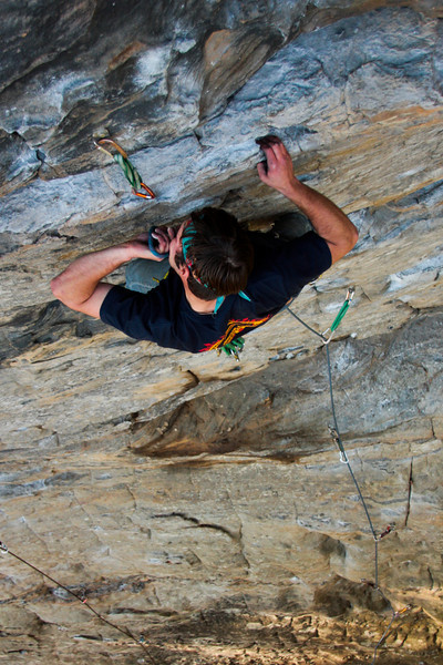 Richard Harrop bites the rope to make a clip on a 5.10.