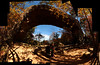 A sloppily stitched photo showing the entirety of Natural Bridge, with Jess and Tracy in the foreground.