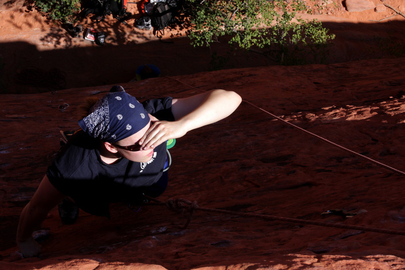 Jess shades her eyes and looks for holds at the top of a route in Red Rocks.