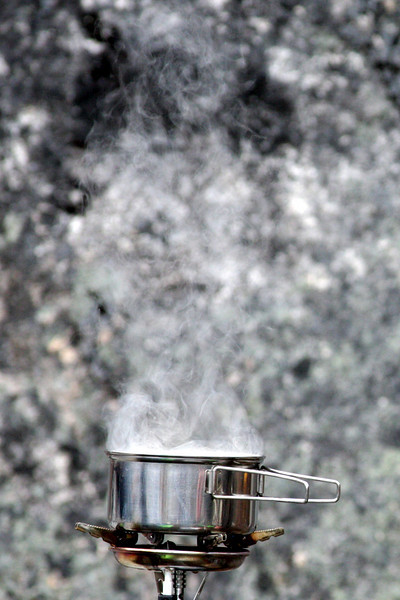 A pot of soup simmers slowly away against a giant granite backdrop.