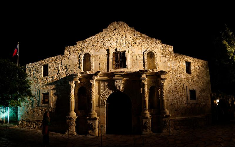 Tracy stands in front of a slightly poorly stitched panoramic photo of the Alamo.