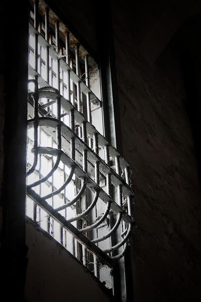 A barred window lets in a little light overhead.