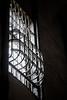 A barred window lets in a little light overhead.