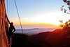 A three-image stitch of the sunset and Kelsey climbing <i>T-Crack 5.10</i>.