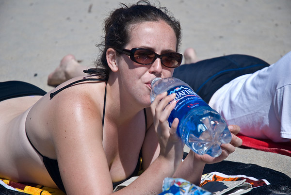 Sasha replenishing her agua while laying out at the beach