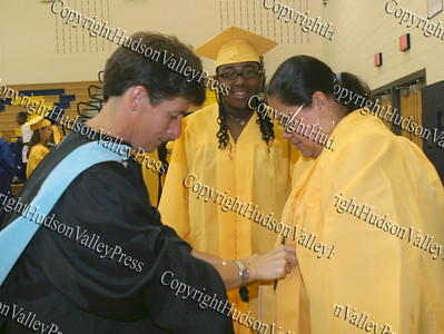 Cindy Pomarico helps Ashley Rivera with her gown as Latoya Winston looks on prior to Beacon's graduation.
