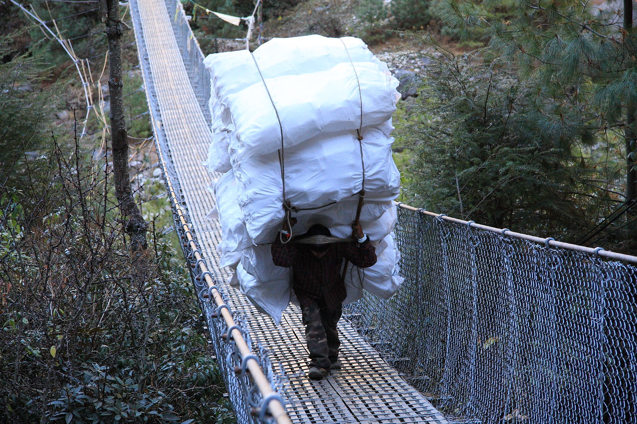 Man with same loads of plastic materials almost a month later hauling them across suspension bridge.  We never did find out what they actually were.