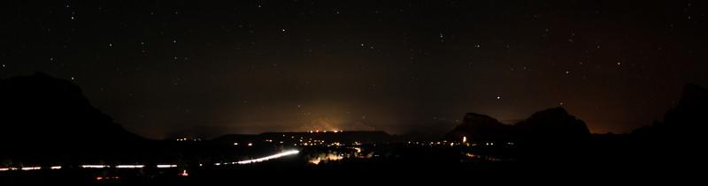 The town of Sedona glows faintly from afar in the early night.