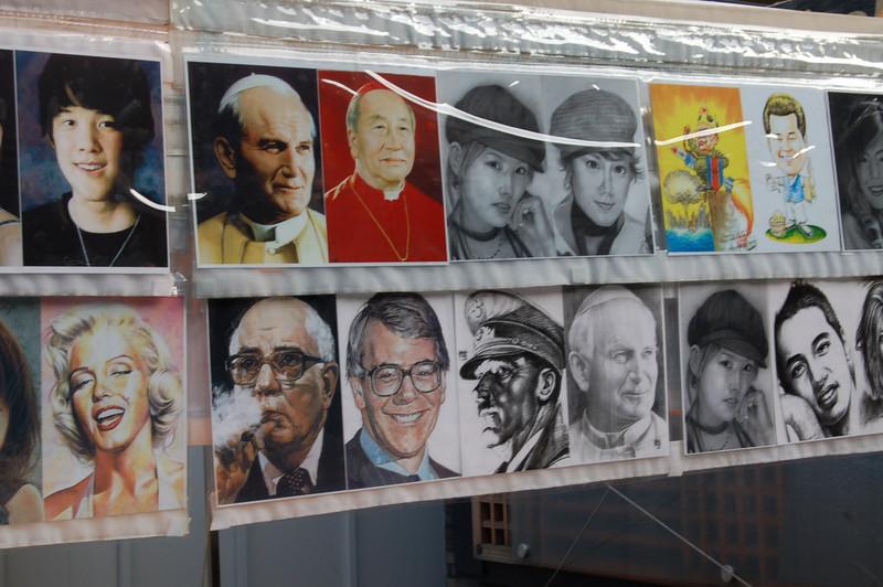Why would a street artist in Seoul illustrate his skills with a portrait of John Major?