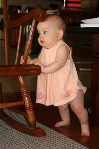 Anna loves to pull up on the rocking chair