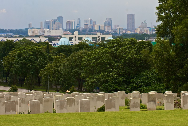 The Kranji War Memorial is on the north side of the island of Singapore, closer to Johor Bahru (JB) in Malaysia than to the 'Downtown Core' area of Singapore. But that's not saying much: the island is only about eight miles north–south. Here the high-rise buildings of downtown Singapore are seen from the wet hill of the Commonwealth war graveyard.