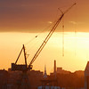 A crane at an East Boston shipyard is  by setting sun dropping under a bank of clouds.