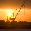 A crane at an East Boston shipyard is silhouetted by the setting sun dropping under a bank of clouds.