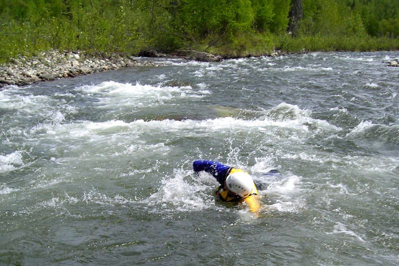 Jon King swims the rapids toward our submerged boulder safe-haven.