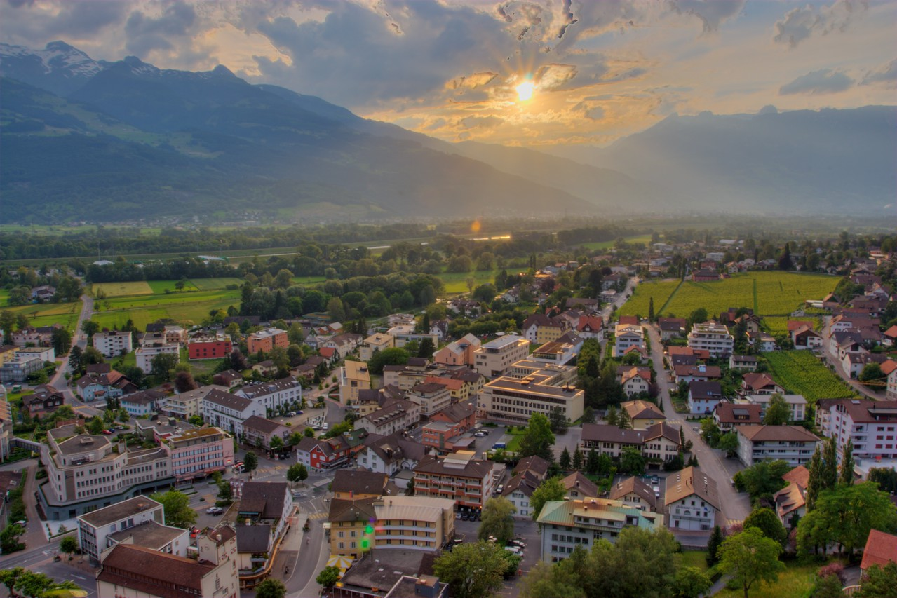 Sunset over toy town • Vaduz, a town with a population of about 5,300, bears the dubious honour of being the capital of the Fürstentum (Principality of) Liechtenstein. The town is very pretty, and thrives from a procession of tourists who want to see such an idiosyncratic country. For many, it seems, all they ever see of Liechtenstein is Vaduz.<br /> <br /> Some of Liechtenstein's industry includes the manufacture of sausage skins, false teeth, anchors, and power tools. I found no evidence to suggest that all of these are made in the same factory, however.