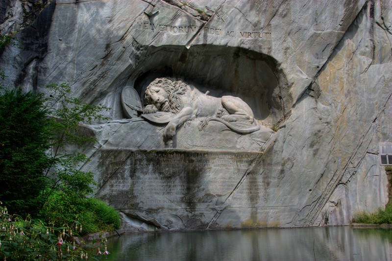 Löwendenkmal • The lion monument commemorates the death of 700 Swiss mercenaries in Paris during the French revolution. <br /> <br /> Here is the text of the monument:<br /> HELVETIORUM FIDEI AC VIRTUTI<br /> Die X Augusti II et III Septembris MDCCXCII<br /> Haec sunt nomina eorum qui ne sacramenti fidem fallerent<br /> [Left column]:<br /> Fortissime pugnantes ceciderunt<br /> Duces XXVI<br /> [Names]<br /> Milites circiter DCCLX<br /> [Right column]:<br /> Solerti amicorum cura cladi superfuerent<br /> Duces XVI<br /> [Names]<br /> Milites circiter CCCL<br /> [Bottom]:<br /> Huius rei gestae cives aere collato perrenne monumentum posuere.<br /> <br /> Translated:<br /> TO THE LOYALTY AND BRAVERY OF THE SWISS<br /> On 10th August and 2nd & 3rd September 1792<br /> Here are the names of those who, so as not to break their oath of loyalty:<br /> [Left column]:<br /> …Died while fighting bravely<br /> 26 Officers<br /> [Names]<br /> About 760 soldiers.<br /> [Right column]:<br /> …Survived the battle because of  the care and attention of their friends:<br /> 16 Officers<br /> [Names]<br /> About 350 soldiers<br /> [Bottom]:<br /> The citizens [of Lucerne] have put up this monument as an everlasting commemoration of this event.<br /> <br /> The Rough Guide has this to say on the location: 'This would be a movingly tranquil spot, with its foliage and gently rippling pool in front, were it not for the fact that it's the single most touristed place in the entire city.' Sure enough, when i was there, there were several large Japanese tour-groups having their photos taken in front of the monument.
