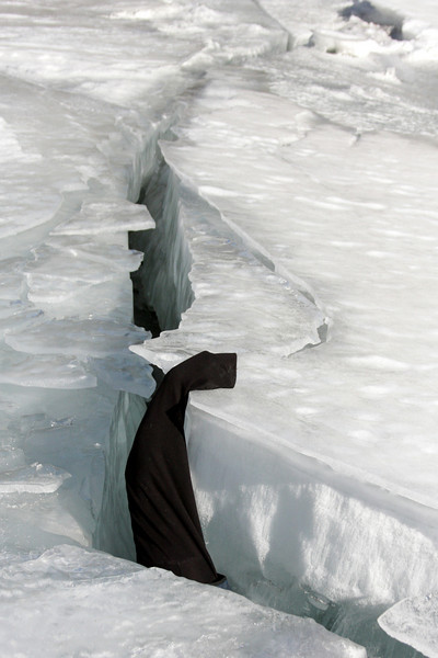 Kelsey's cold hand rises from a giant crack in the river ice.