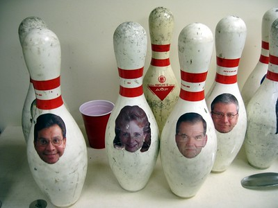 Bowling pins in the anteroom of the bowling alley show the faces of former White House officials