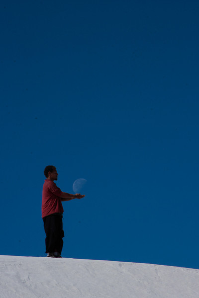 Kelsey holds the moon in his hands atop a dune of white sand.