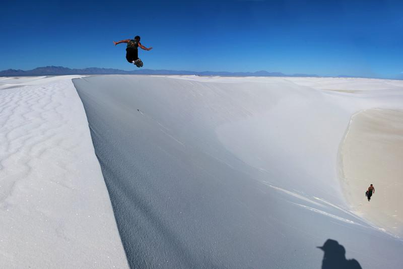 A stitched panorama of Kelsey taking off down a dune, and walking away after the jump at the bottom.