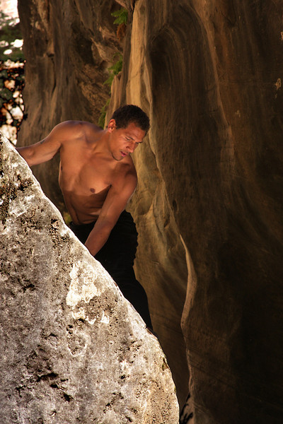 Reflecting sunlight illuminates Kelsey as he searches for holds, bouldering around above a slow spot in the creek.