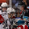 Americans Kruise Reddick and Brett Plouffe work to get control of the puck from Kelowna Rockets Kyle St. Denis
