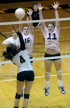 Monticello's Christine Archer (4) returns the ball as Western's Amanda Gough (16) and Chastity Lacy (11) guard at the net. photo Ashley Twiggs