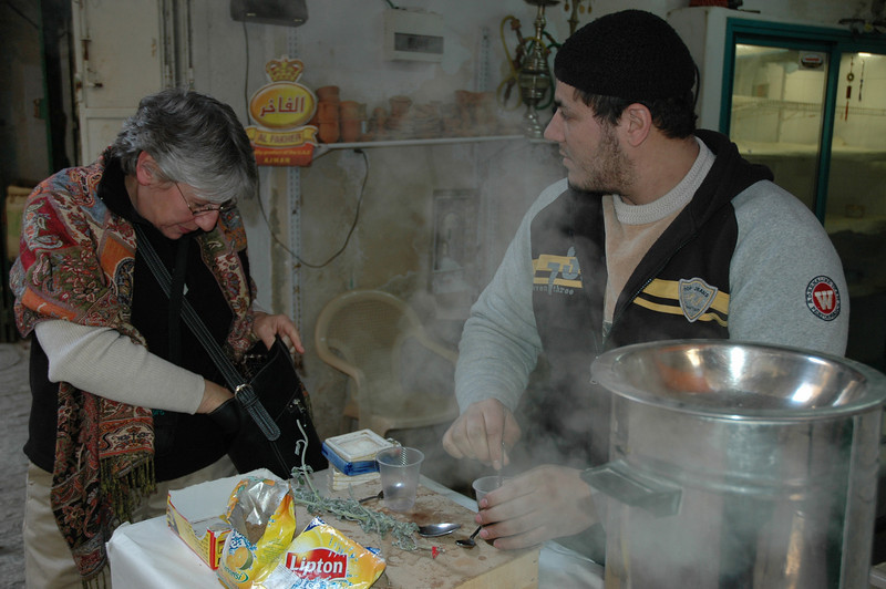 Marcia Johnson, ELCA Synodical Relations staff, buys some coffee from a street vendor in Hebron.