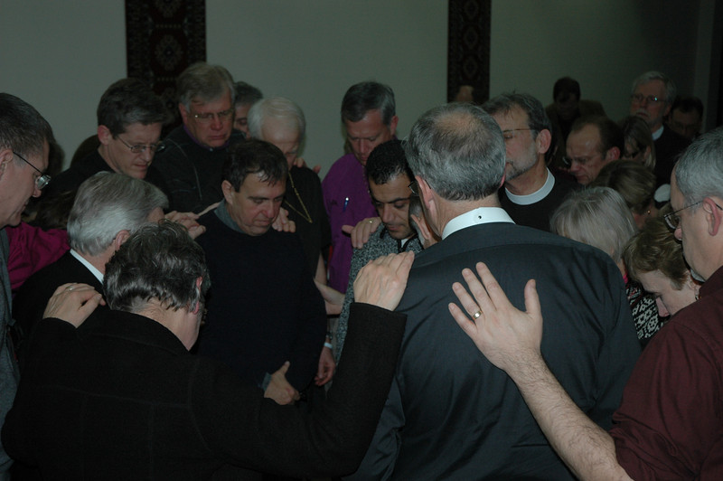 Bishops and clergy from the United States and Canada pray for Rami Elhanan and Mazen Faraj following their presentation to the bishops Jan. 7.  The two men are members of The Parents Circle, Israeli-Palestinian Bereaved Families for Peace.