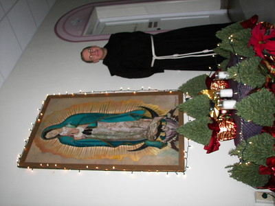 Our pastor, Fr. Chuck, beside Our Lady of Guadalupe decorated for the season.