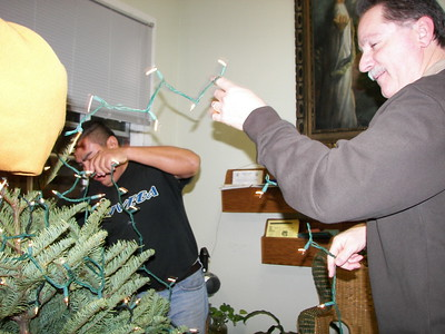 Paciano and Larry work on the Christmas tree lights.