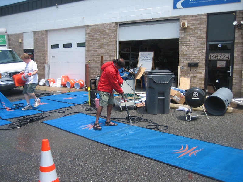 Prashant Sansgiry uses Bob Price's powerwasher to remove the top layer of grime from the mats and the top layer of skin from his feet.