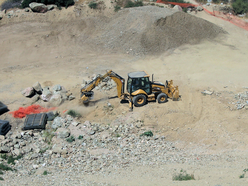 5/08 The backhoe has a slotted shovel for separating rocks from dirt.  They pick up debris from the foot of the slide, shake it (note dust) and dump into piles.