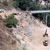 7/28 Overview.  Lunchtime.  They are now putting in the wire mesh and fill above the rock wall.