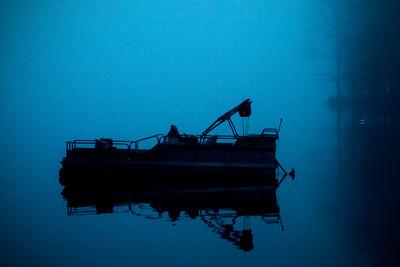 Boat before sunrise in the fog