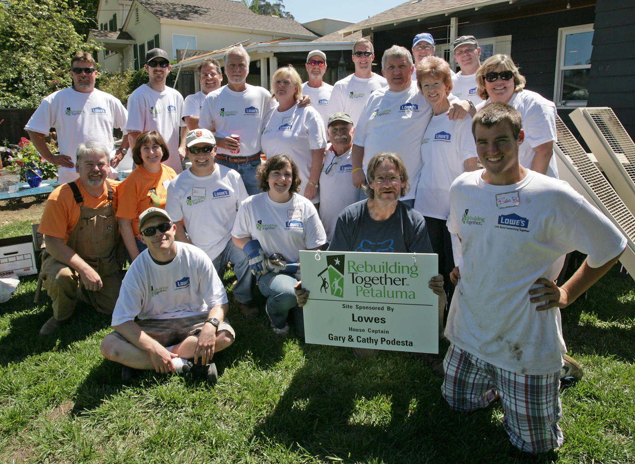 Homeowner Leland Gilardi holding sign surrounded by volunteers
