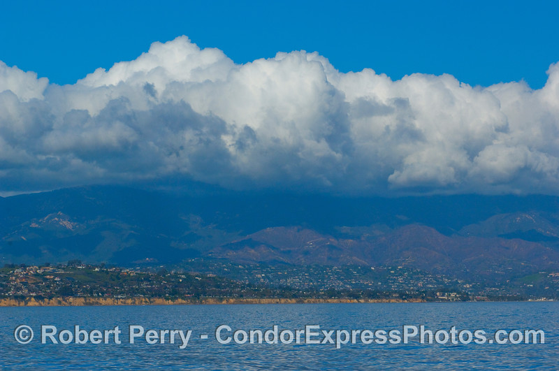 Looking north at Santa Barbara with storm clouds above the mountains.  Burn area clearly visible from recent fire.